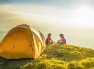 Kids in colorful outdoor clothing sitting beside a bright yellow dome tent camped in an idyllic mountain top meadow illuminated by the warm light of a summer sunset. ProPhoto RGB profile for maximum color fidelity and gamut.
