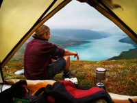 Hiking young man is sitting in front of a picturesque scenic view of lake Gjende and a remote mountain range in the Jotunheimen national park, Norway. Backpacker sitting in front of his tent gazing at stunning view. People traveling. XXXL (Sony Alpha 7R)
